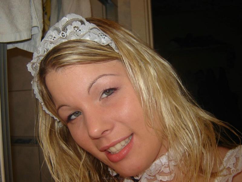Няшная блондинка с пирсингом в языке примеряет наряд сексуальной горничной 16 фото