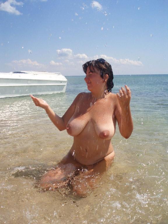 Пухленькая мамаша купается на нудистском пляже 13 фото