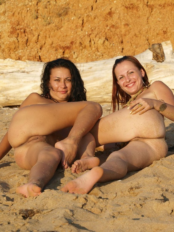 Голые девушки с бусами позируют на песке 4 фото