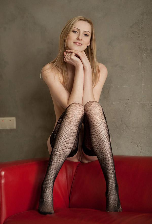 Соло молодой блондинки в чулках на красном диване 5 фото