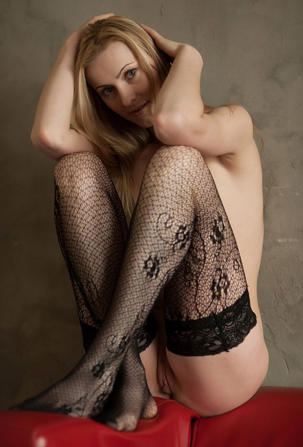 Соло молодой блондинки в чулках на красном диване 6 фото