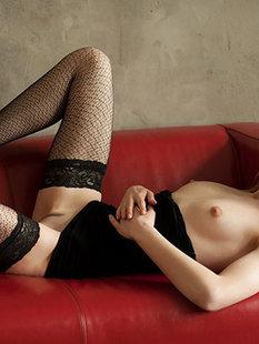 Соло молодой блондинки в чулках на красном диване
