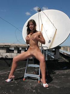 Голая девушка забралась на крышу и светит телом около антенны