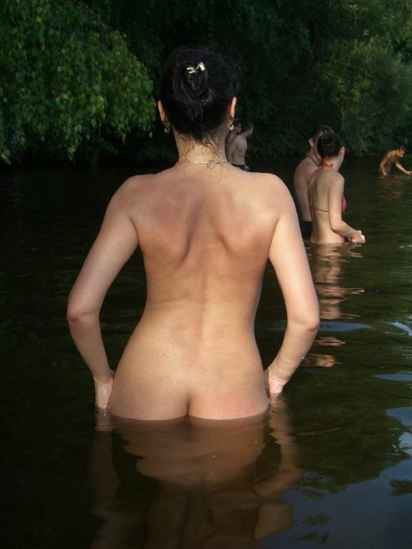 Голая брюнетка в очках позирует при людях в реке 8 фото