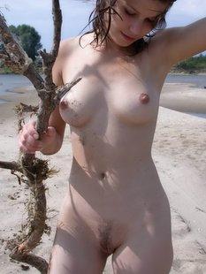Голая брюнетка позирует на жарком песочке