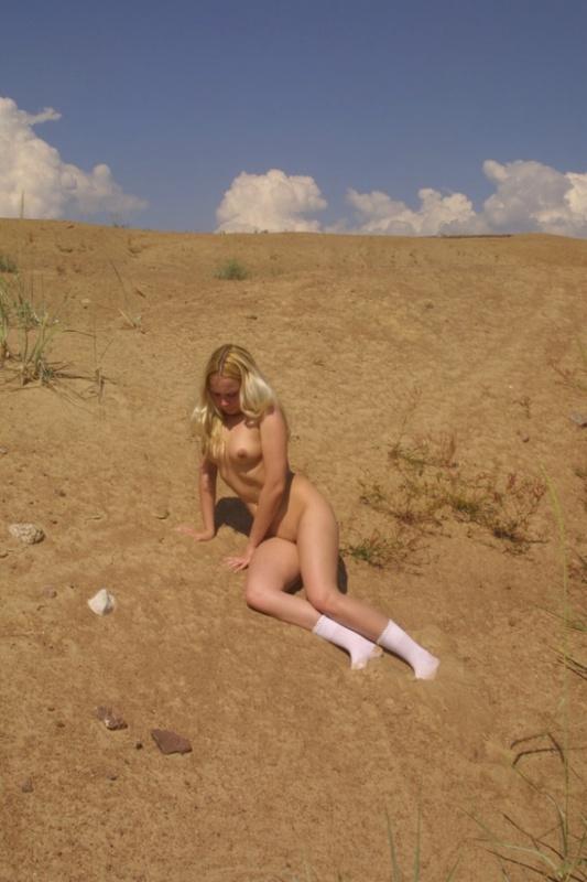 Хрупкая блондинка позирует голышом у стены 6 фото