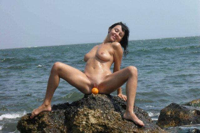 Голая брюнетка позирует на берегу моря 5 фото