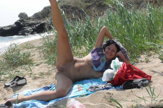 Голая брюнетка позирует на берегу моря 20 фото