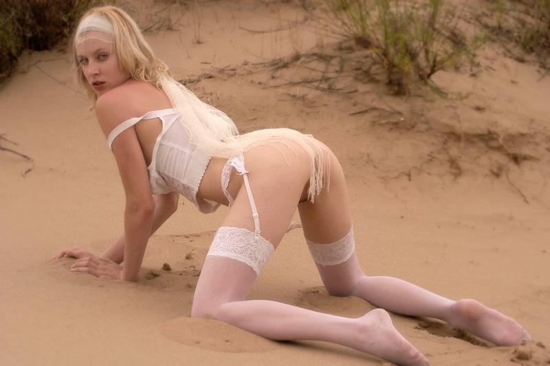 Блондинка в чулках показывает голую киску на песке 7 фото
