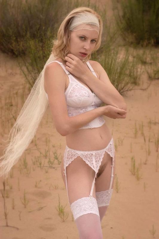 Блондинка в чулках показывает голую киску на песке 1 фото