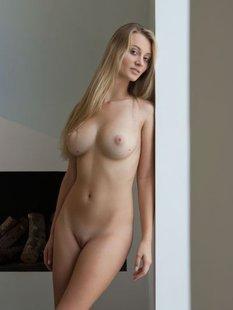 Длинноволосая блондинка светит большими сиськами на диване и стоя