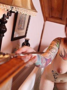Рыжая телка с татуировками принимает ванну с лепестками роз