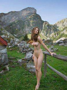 Худая девушка с пышной грудью позирует гола у забора дома в горах