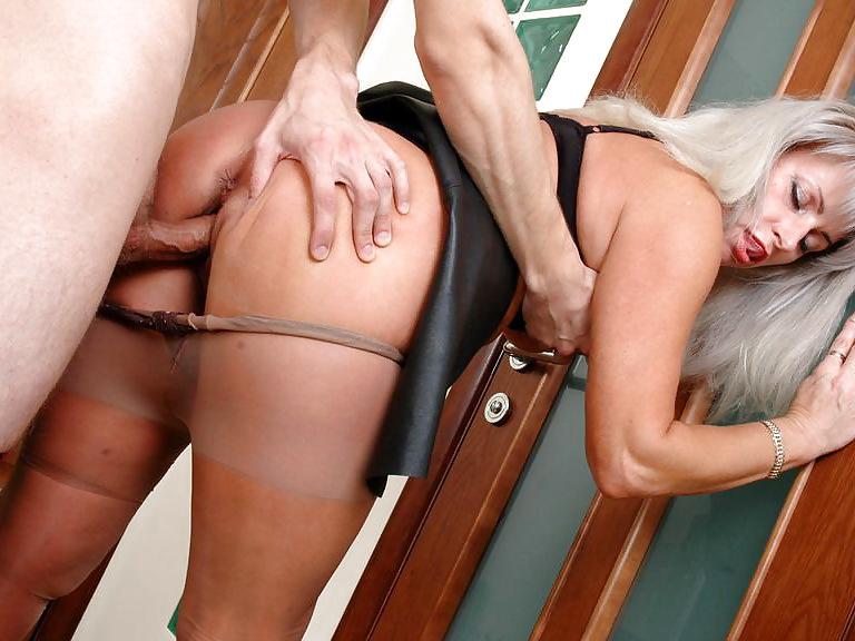 Парень трахает стоя зрелую дамочку в чулках