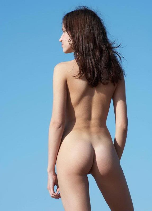 Молодая брюнетка позирует на песке у моря без одежды 14 фото