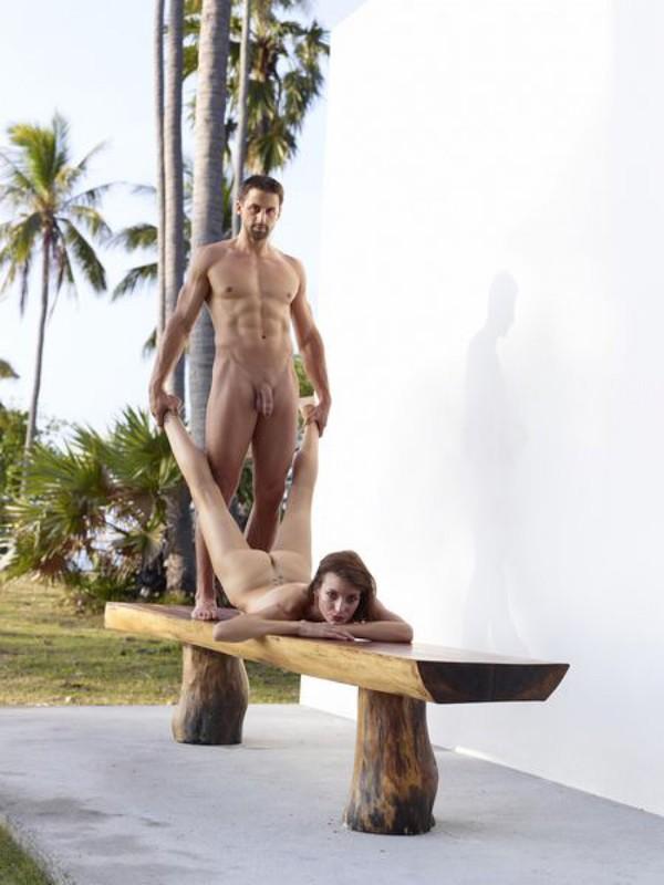 Качок помогает голой жене-гимнастке тренироваться на лавке в саду 4 фото