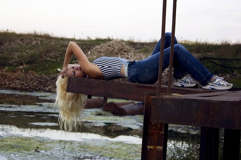 Молодая блондинка сидит, раздвинув ноги на белой кровати 5 фото