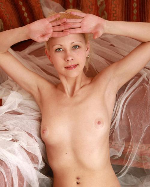 Молодая блондинка сидит, раздвинув ноги на белой кровати 14 фото