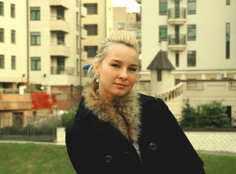 Татуированная блондинка в джинсах и с голой грудью стоит у стены 1 фото