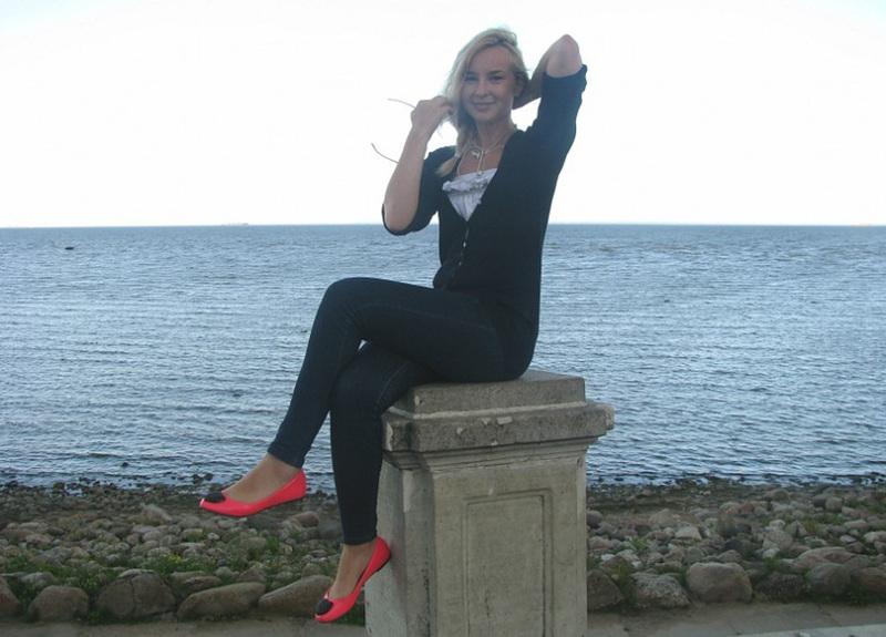 Татуированная блондинка в джинсах и с голой грудью стоит у стены 5 фото