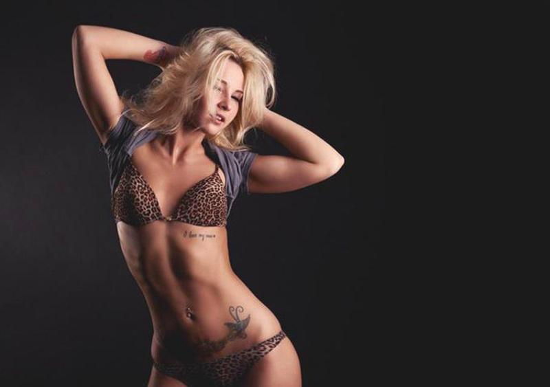 Татуированная блондинка в джинсах и с голой грудью стоит у стены 9 фото