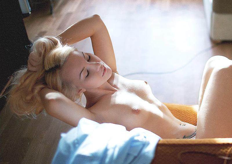 Татуированная блондинка в джинсах и с голой грудью стоит у стены 14 фото