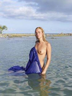Обнаженная девушка с синей тряпкой на море