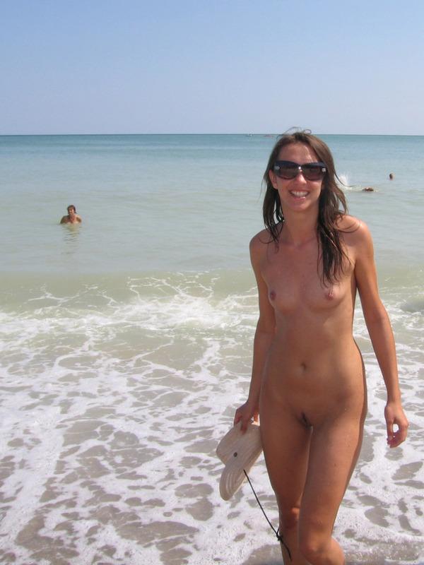 Длинноногая телка голышом загорает на нудистском пляже 5 фото