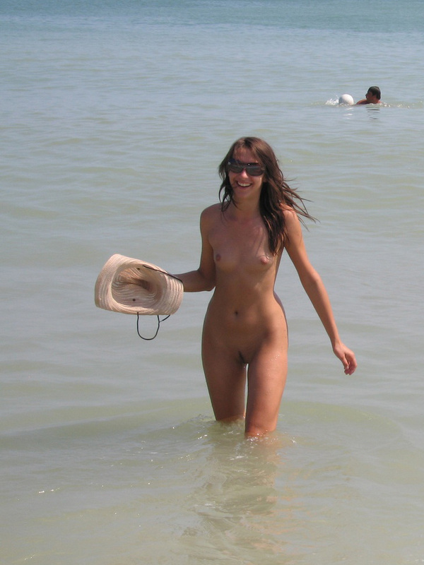 Длинноногая телка голышом загорает на нудистском пляже 2 фото