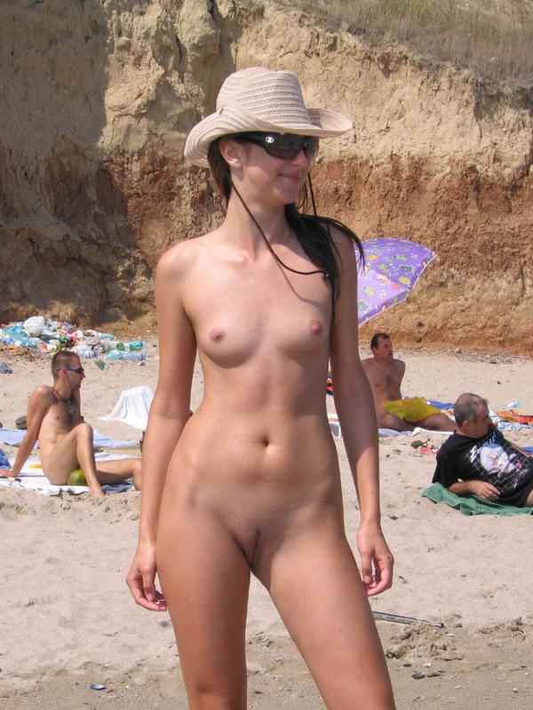 Длинноногая телка голышом загорает на нудистском пляже 9 фото