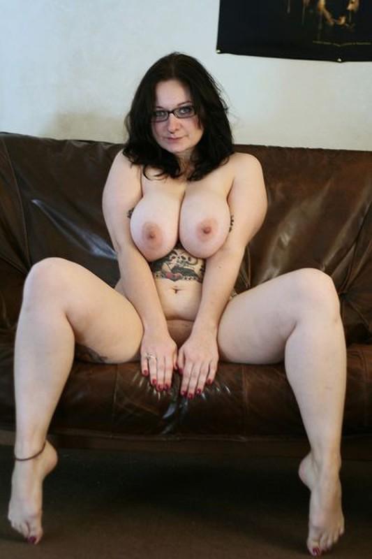 Полная мамочка с огромными дойками и татухами позирует на кожаном диване 17 фото