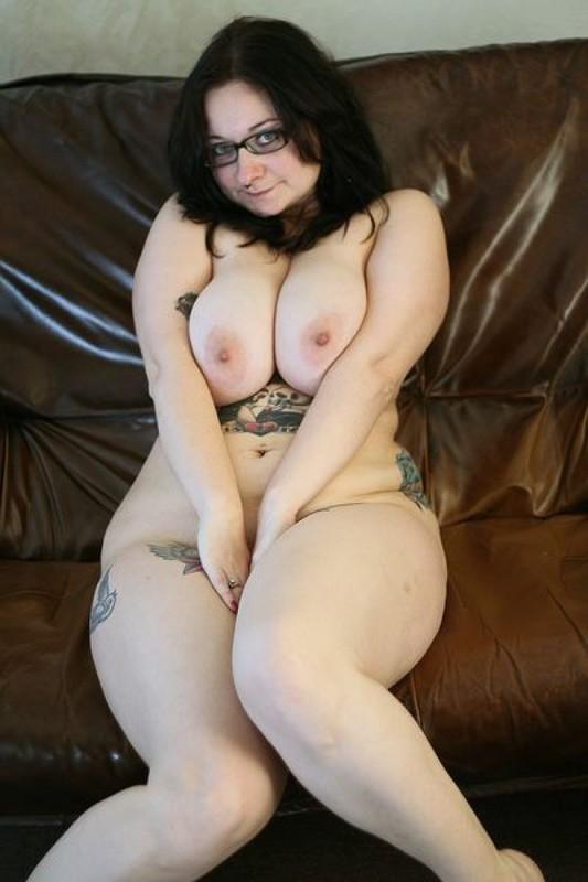 Полная мамочка с огромными дойками и татухами позирует на кожаном диване 6 фото