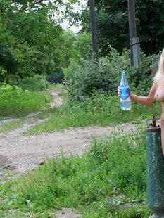 Голая девушка собирается набрать воды в колонке
