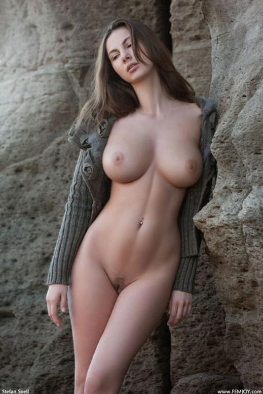 Эромодель с большой натуральной грудью позирует в скалах оголив 26 фото
