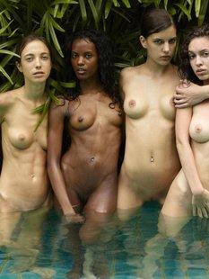 Обнаженные молодые девушки позируют стоя в бассейне