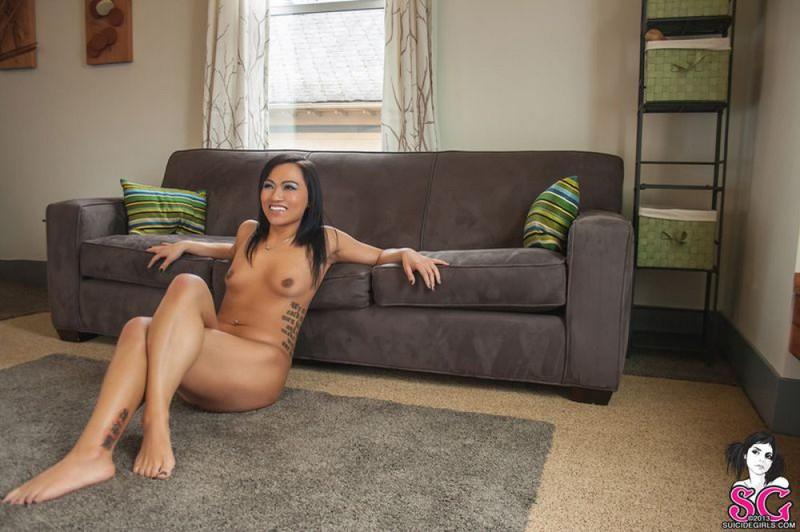 Красивая брюнетка с татуировками раздевается и позирует дома на диване 4 фото