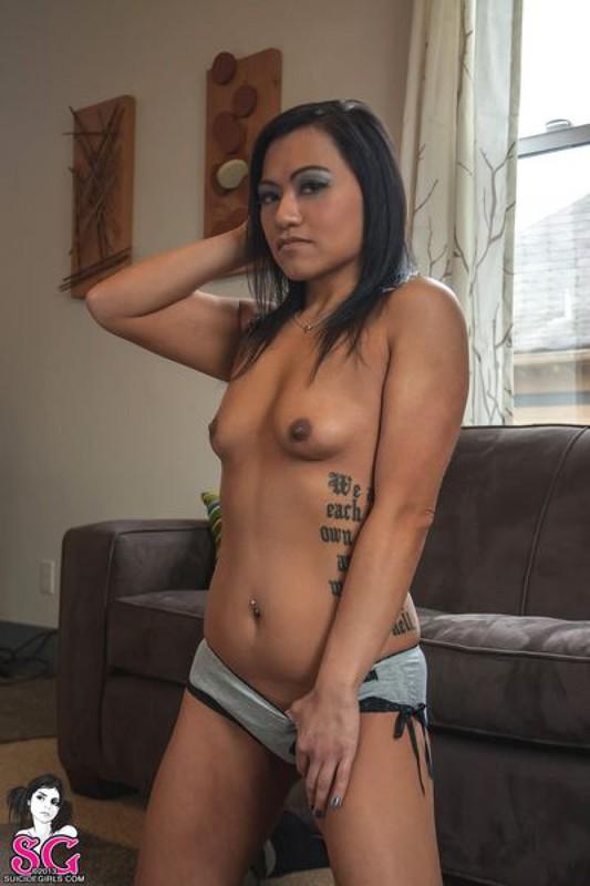 Красивая брюнетка с татуировками раздевается и позирует дома на диване 16 фото