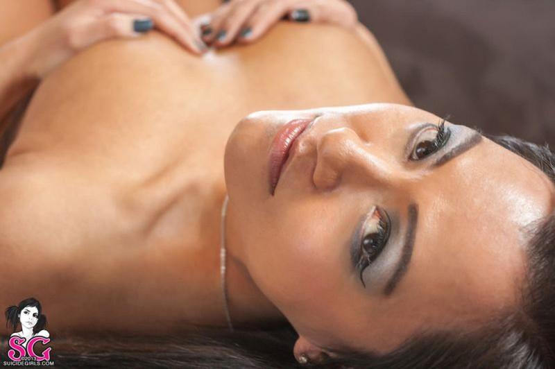 Красивая брюнетка с татуировками раздевается и позирует дома на диване 21 фото