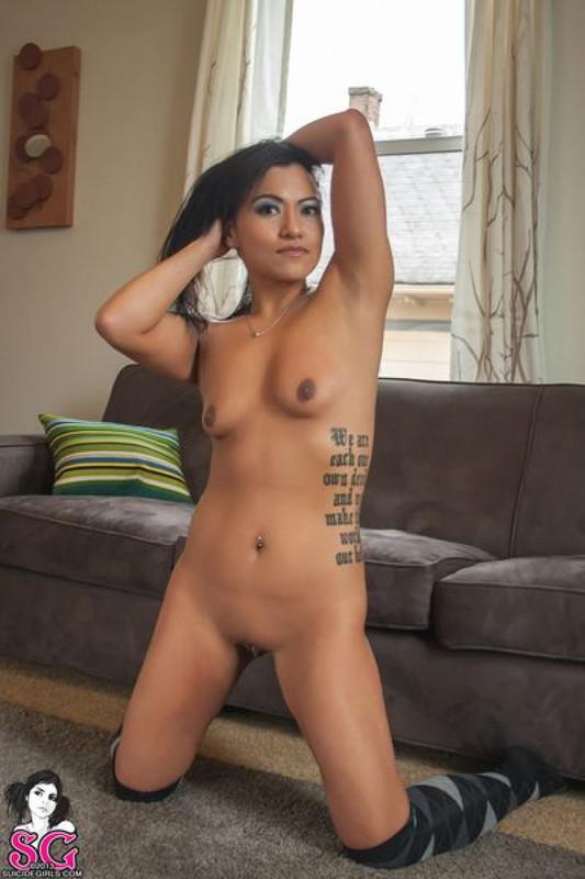 Красивая брюнетка с татуировками раздевается и позирует дома на диване 27 фото