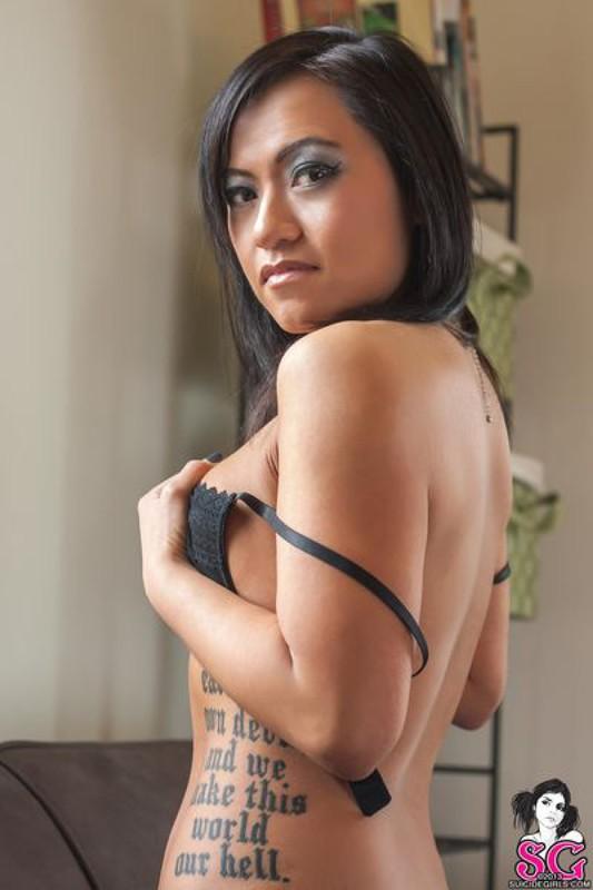 Красивая брюнетка с татуировками раздевается и позирует дома на диване 24 фото