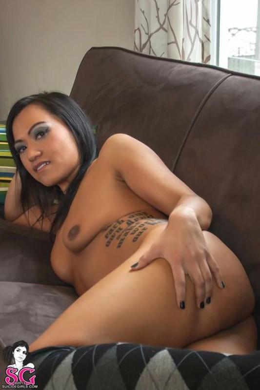 Красивая брюнетка с татуировками раздевается и позирует дома на диване 36 фото