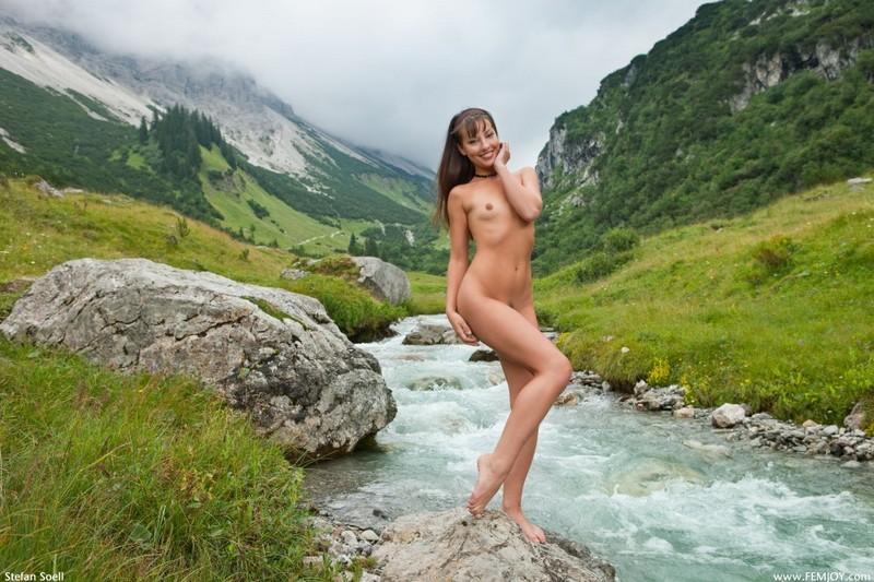 Голая телка светит стройным телом на речном булыжнике в горах 2 фото