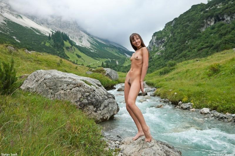 Голая телка светит стройным телом на речном булыжнике в горах 1 фото