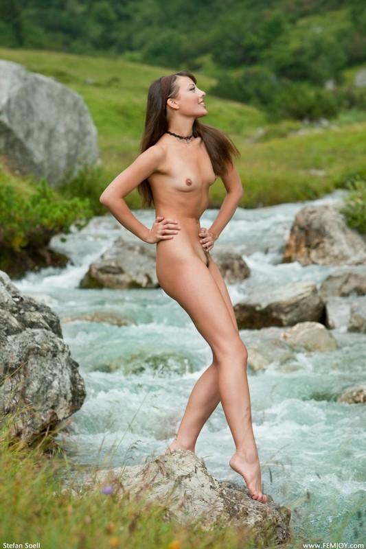 Голая телка светит стройным телом на речном булыжнике в горах 9 фото