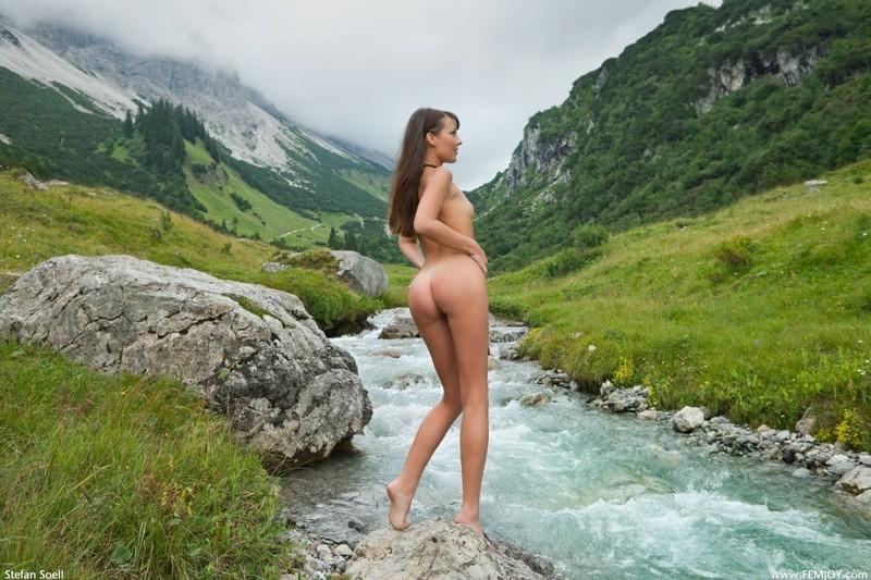 Голая телка светит стройным телом на речном булыжнике в горах 4 фото