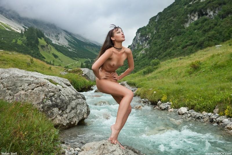 Голая телка светит стройным телом на речном булыжнике в горах 16 фото