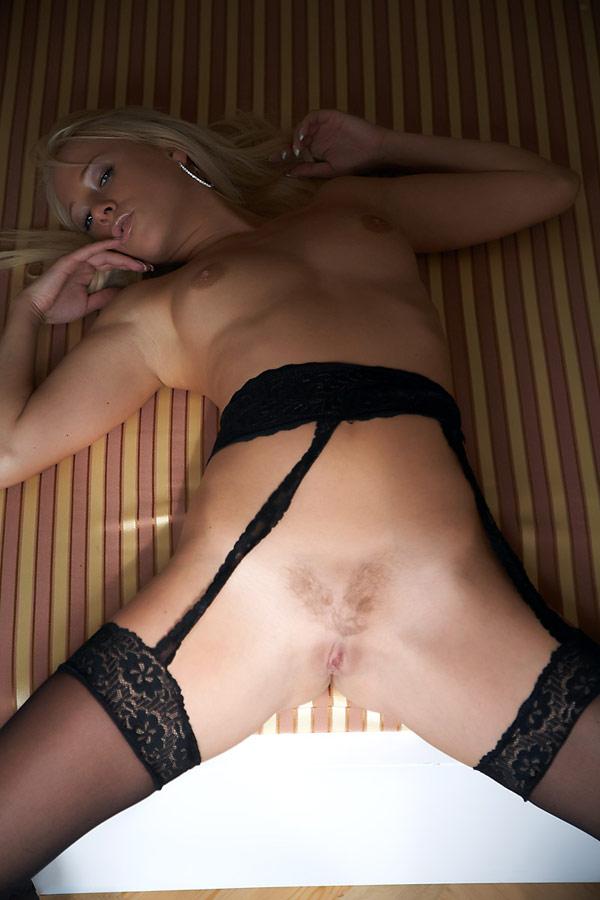 Худенькая блондинка красиво позирует на камеру в чулках 6 фото