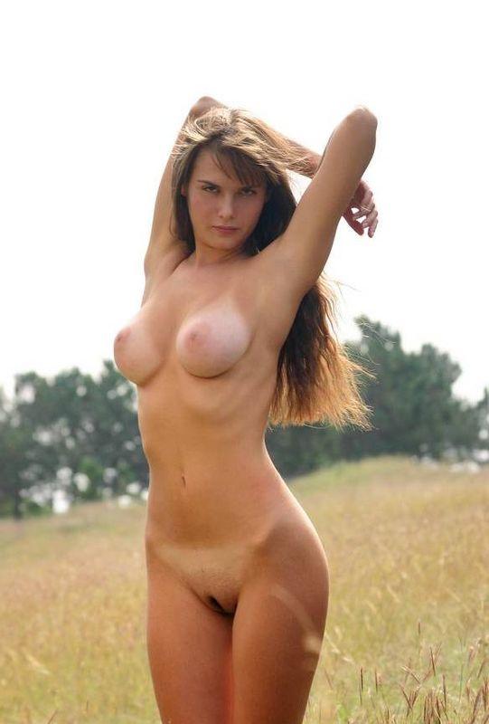 Голая грудастая брюнетка красиво позирует в поле 1 фото