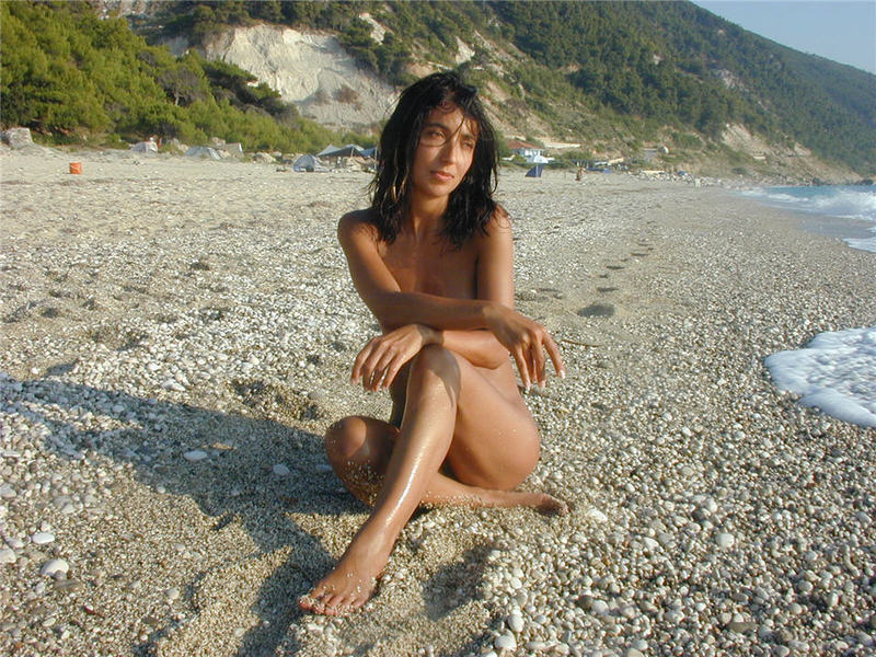 Стройная брюнетка гуляет на нудистском пляже 11 фото