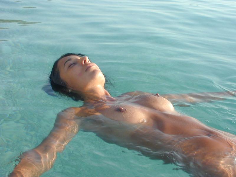 Стройная брюнетка гуляет на нудистском пляже 16 фото